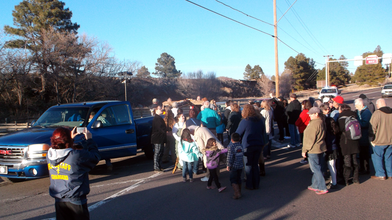 The crowd lifts the cross in preparation for its journey down Route 66