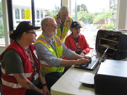 During the Cascadia Rising earthquake exercise in the Pacific Northwest, Island County Amateur Radio Club members John Acton, K7ACT (seated, in yellow vest), types a Red Cross emergency message via a 2 meter packet link, while Bill Frederick, KF7BMK (standing, with handheld), monitors a VHF simplex voice net at a field triage and treatment facility on Whidbey Island. Red Cross volunteers Kendra O'Bryan (left) and Patty Cheek (right) help coordinate the message traffic flow. [Vince Bond, K7NA, photo]